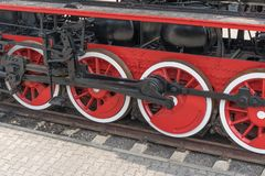 Old steam train wheels approaching, close-up. Black and red wheels. Rails and sleeper stock photos