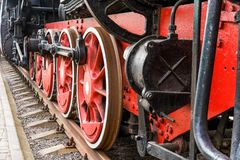 Old steam train wheels approaching, close-up. Black and red wheels. Rails and sleepers. stock photos