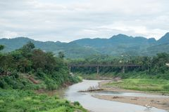Old steel bridge across the river. River side is forested,the sky is Cloud, Luang Prabang Loas Stock Photos