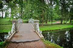 Old steel bridge over flow in the palace park in Gatchina Stock Photos