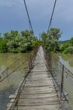Old steel cable and wooden footbridge across river. Wooden suspension bridge. Stock Photo