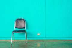 Old steel chair on green wall Stock Photo
