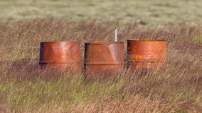 Old steel drums in a field Royalty Free Stock Photos