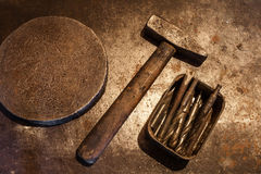 Old steel hammer with wooden handle, iron heavy ring and drill bits for metal in the box on the metal background. The old steel hammer with wooden handle, iron Royalty Free Stock Photos