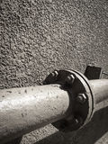 Old steel pipes on rough wall. Royalty Free Stock Photography