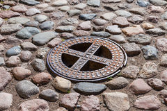 Old steel sewer manhole on the cobblestone road Royalty Free Stock Photography