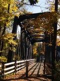 Old steel-truss footbridge. Old steel-truss pedestrian bridge in late afternoon autumn sun stock photography