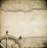 Old steering wheel and torn nautical map Stock Photo