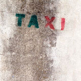 Old stencil taxi sign on the wall Stock Photography