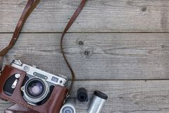 Old still camera in brown leather case on wooden desk. Old still camera in brown leather case on wooden table Royalty Free Stock Images