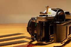 An old still working camera, his films to be developed. His telephoto lenses and wide-angles, his flash royalty free stock image