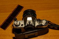 An old still working camera, his films to be developed. His telephoto lenses and wide-angles, his flash royalty free stock images
