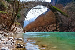 Old stone arch bridge over Aoos river, in Konitsa, Greece Royalty Free Stock Photos