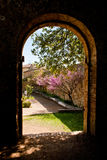 Old stone arch and garden. An old stone arch and a garden with flowers in San Quirico d'Orcia Stock Photography