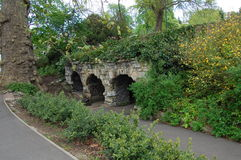 Old stone arches covered in greenery. Stock Photo