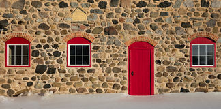Old Stone Barn with Bright Red Door and Three Windows Royalty Free Stock Image