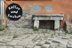 Old stone bench in front of a bakery with a sign Coffee and , alte Steinbank vor Bäckerei Schild Kaffee und Kuchen Royalty Free Stock Photos