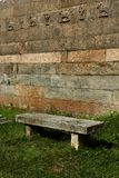 A old stone bench on the grass field Stock Image