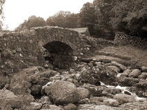 Old Stone Bridge. An old stone bridge in the Lake District of england, given a sepia toning to give an aged feel Royalty Free Stock Image