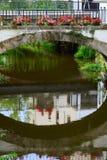 Old stone bridge. On stream Leuk ( too Leukbach ) and geranium flowers in Saarburg, Rheinland-Pfalz, Germany, summer Stock Photography