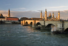 Old stone bridge across Ebro river in Zaragoza. In early morning lights of sunrise,  Basilica–Cathedral of Our Lady of the Pillar is behind.  Cathedral of Stock Images