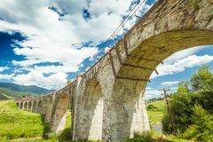 Old stone bridge on a background of blue sky. Summer day Stock Photo