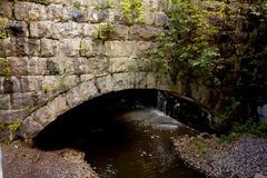 Old stone bridge coverd with moss and torrential river. Old stone bridge coverd with moss and torrential river royalty free stock photography