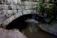 Old stone bridge coverd with moss and torrential river. Old stone bridge coverd with moss and torrential river stock photos