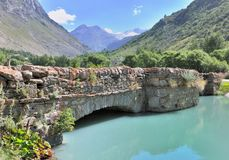 Stone bridge cross a river. Old stone bridge cross a blue river in mountain in summer royalty free stock image