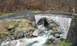 Old stone bridge crossing a wild river with trail markers and hiking trails on both sides. An old stone bridge crossing a wild river with trail markers and royalty free stock photo
