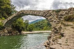 Old stone bridge. An old stone bridge across a small montain river Stock Photos