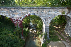 Old stone bridge over creek. Center view of old stone bridge with red vine built in 1874 off of route 66 Royalty Free Stock Images