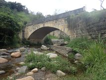 Old stone bridge over a river in Colombia Stock Photo