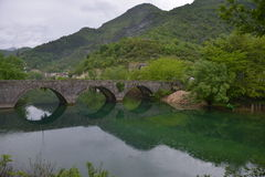 The old stone bridge. Over the river of Crnojevic near the coast of Skadar lake with green waters, boats and plants on its bank in the rain Royalty Free Stock Images
