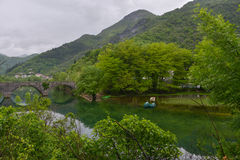 The old stone bridge. Over the river of Crnojevic near the coast of Skadar lake with green waters, boats and plants on its bank in the rain Royalty Free Stock Photos