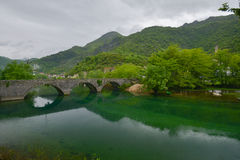 Old stone bridge over River Crnojevic. The old stone bridge over the river of Crnojevic near the coast of Skadar lake with green waters, boats and plants on its Stock Photos