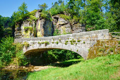 Old stone bridge over a small rivulet Royalty Free Stock Image