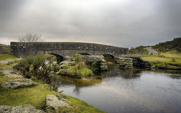 A Stone Bridge in Dartmoor. An old stone bridge with the remains of an ancient granite clapper bridge over a river in Dartmoor National Park in Devon Stock Image