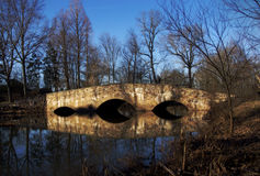 Old Stone Bridge. An old, stone bridge stretches across a small stream with it's image mirrored in the water as a clear blue winter sky provides a backdrop to Stock Images
