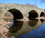 Old Stone Bridge with Three Arches. Reflecting in water.  Reflection of arches forms circles in water Royalty Free Stock Photography