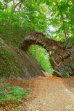 Old stone bridge in the woods Stock Photo