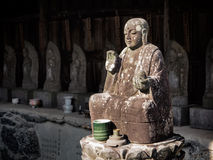 Old stone buddhist statue of a meditating Buddha. In a temple Stock Image