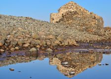 Old stone building reflected in the saltwater Stock Photos