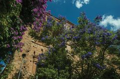 Old stone building and trees with colorful flowers at Caceres. Old stone building and trees with colorful flowers in a sunny day at Caceres. A cute and charming stock photography