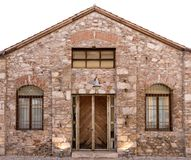 Old stone building with wooden door and two windows with bars. stock image