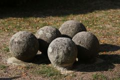 Old gray cannonballs lie on the ground. Old stone cannonballs lying on the ground royalty free stock photo