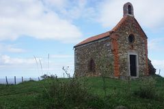 Old chapel on a hill in basque country, spain. Old, stone chapel on a green hill in basque country, spain stock image