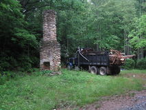 Old stone chimney and logging truck. An old stone chimney and logging truck in a green forested landscape in the Appalachian Mountains Royalty Free Stock Photography