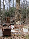 Old stone chimney surrounded by junk in forest. An old stone chimney surrounded by discarded junk items in a winter forested landscape in the southern Stock Images