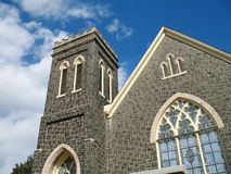 Old stone church. Portion of old gray fieldstone church with stained-glass window Stock Images